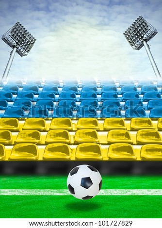 Ukraine flag pattern on seats at outdoor sport stadium with soccer ball. - stock photo