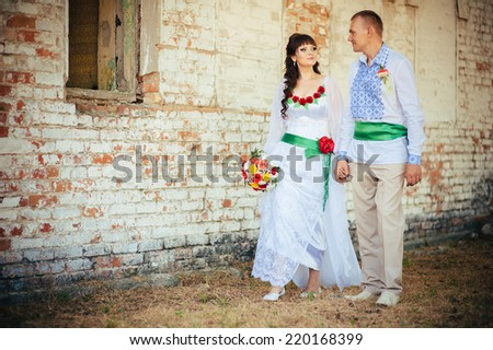 Ukraine. Happy ukrainian wedding (bridal) couple in the ukrainian style. Beautiful bride and groom in the ukrainian style are standing with bouquet. Female and male models.  park summer outdoor