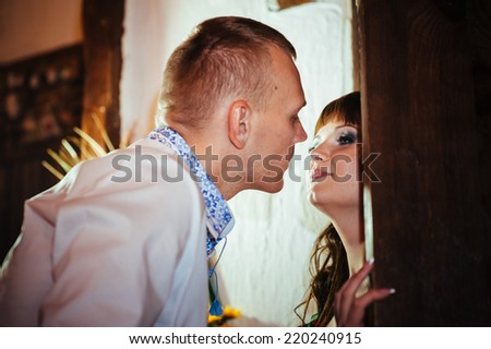 Ukraine. Happy ukrainian wedding (bridal) couple in the ukrainian style. Beautiful bride and groom in the ukrainian style are standing with bouquet. Female and male models. Indoors, close up.