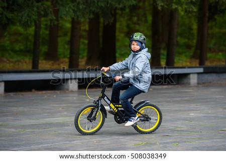 Ukraine, Kharkov - September 24, 2016: Schoolboy is riding a bike in Kharkov park