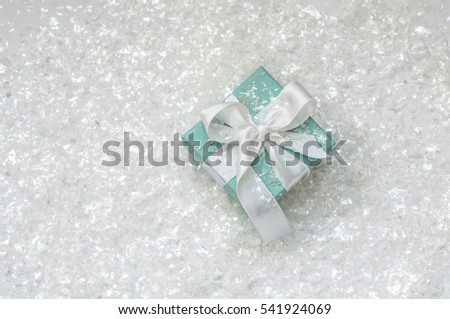 Ukraine, Kiev - December 23, 2016: Tiffany box tied with silk ribbon, sprinkled with artificial snow on a white background, top view