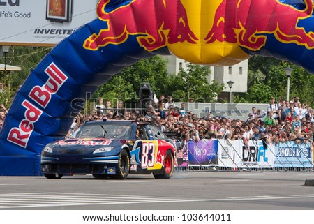 UKRAINE,KIEV - MAY 19: Daniel Ricciardo drive a NASCAR of Red Bull Racing Fires Up the Streets of Kiev making even more smoke and noise, Champions Parade, May 19, 2012 in Kiev, Ukraine - stock photo