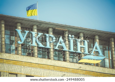 "UKRAINE, KIEV - 13 MAY 2011: Inscription ""Ukraine"" on the building and the state flag of Ukraine in the center of Kiev's Independence Square  - stock photo"