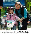 UKRAINE, KIEV - SEPTEMBER 11: Young biker girl with mother, at the child amateur bicycle competition We are the champions, on September 11, 2010 at Ukraine, Kiev. - stock photo