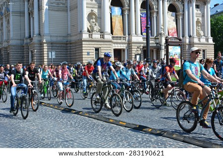 UKRAINE, LVIV - May 30, 2015: People ride their bikes during the mass bike ride Cycle Day at Svobody Avenue with Lviv Opera House (The Lviv Theatre of Opera and Ballet) behing.