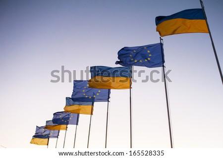 Ukrainian and European flags on blue sky. revolution - stock photo
