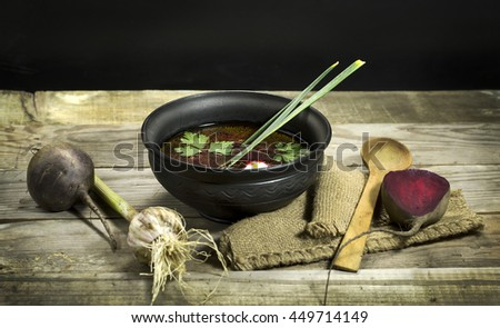 Ukrainian borscht with beet, garlic and a spoon on a wooden background