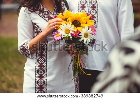ukrainian bride in native embroidery holding beautiful colorful autumn bouquet - stock photo