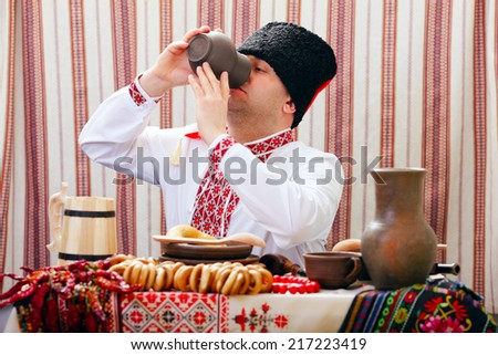 Ukrainian Cossack eats at the table and smokes a pipe smoking - stock photo