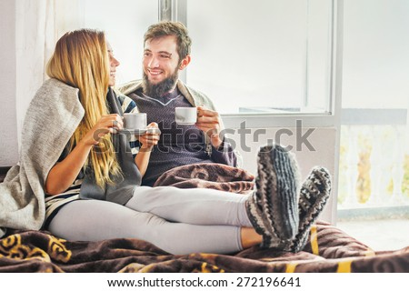 ukrainian couple  drinking tea on their bed - stock photo