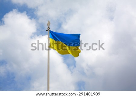 Ukrainian flag on a flagpole in the wind develops in the background of the sky. - stock photo