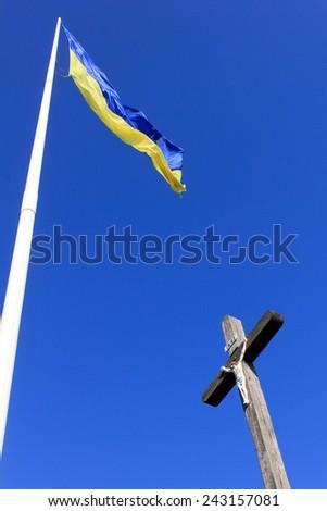 Ukrainian flag waiving above the wooden cross in Khust, Ukraine  - stock photo