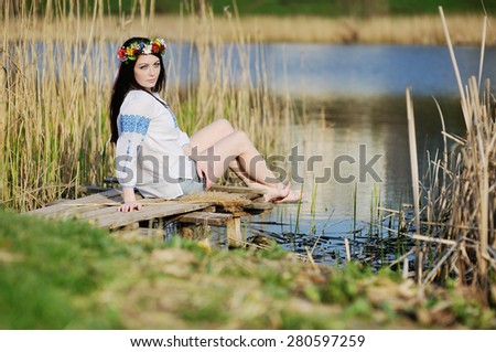 Ukrainian girl in shirt sitting on the bridge in the background of the river - stock photo
