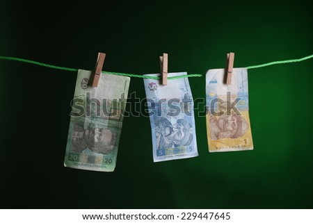 Ukrainian hryvnia bills hanging on rope attached with clothes pins. Money-laundering concept. On dark color background - stock photo