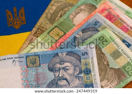 Ukrainian money against the background of the national flag