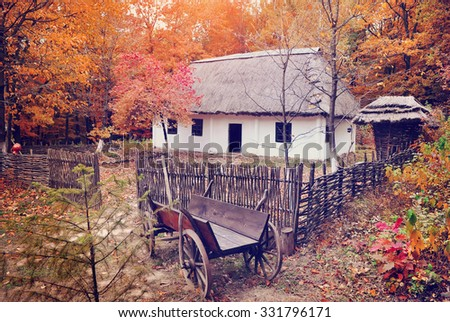 Ukrainian Museum of Life and Architecture. Ancient hut with a straw roof and wooden cart - stock photo