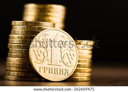 Ukrainian one hryvnia coin and gold money on the desk  - stock photo