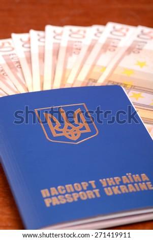 ukrainian passport and one hundred euro banknotes - stock photo