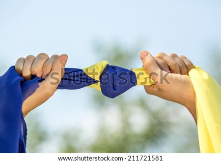 Ukrainian patriot hold tapes of ukrainian flag over sky. daylight - stock photo