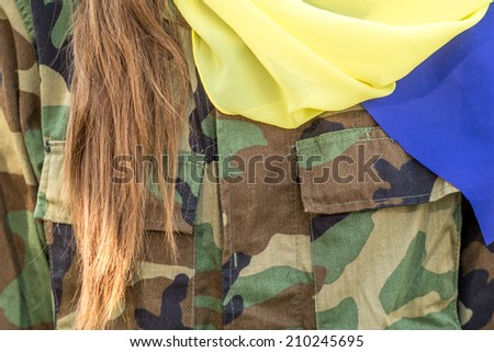 Ukrainian patriot in military uniform and with ukrainian flag. closeup - stock photo