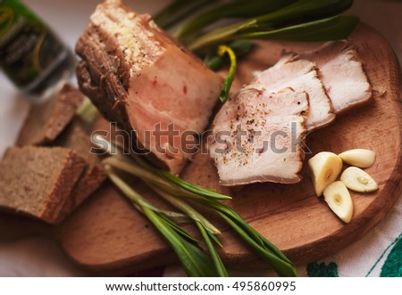 Ukrainian traditional food - salo. Sliced bacon with garlic, onion, bread and spice on wooden background