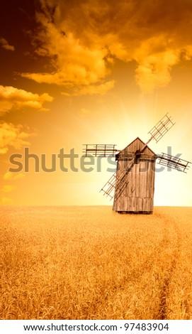 Ukrainian traditional windmill and field of ripe wheat at summer sunset - stock photo