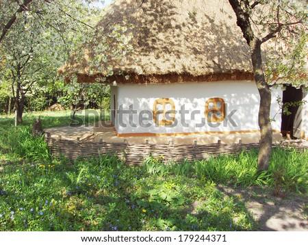 Ukrainian village house in a shady spring garden - stock photo