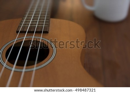 Ukulele guitar and coffee cup on wood table