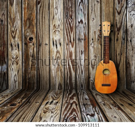 Ukulele in vintage wood room. - stock photo