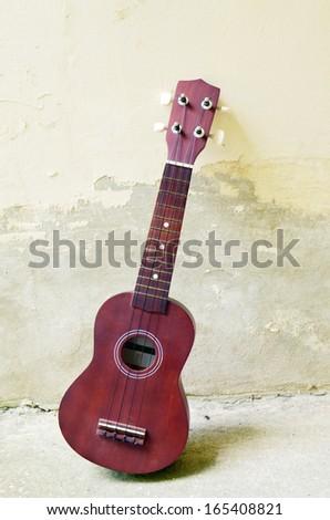 ukulele on concrete background - stock photo