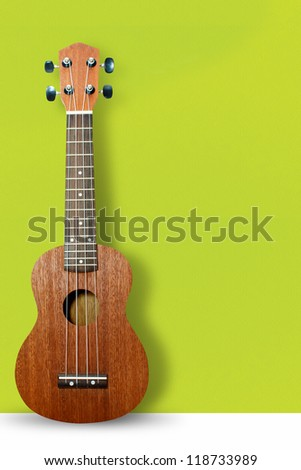 Ukulele on green wall background