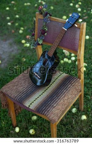 Ukulele on old chair - stock photo