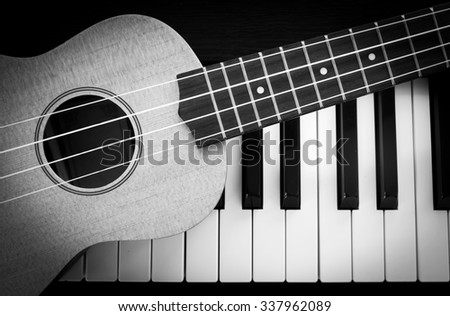 Ukulele on piano key. Top view. Music concept background. Black and white theme. With dark vignette. - stock photo