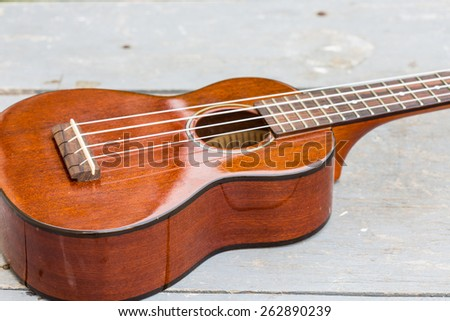 Ukulele on wooden background.