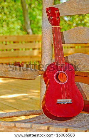 Ukulele string instrument on old rocking chair on porch - stock photo