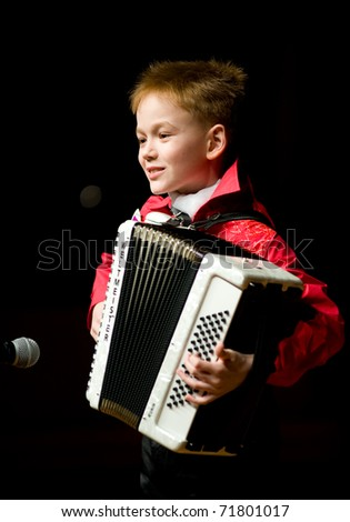 """ULAN-UDE, RUSSIA - APRIL 3: An unidentified participant of the 1st Charity Children's Beauty and Talents Contest """"Star Land"""", shows his talent - playing the accordion, April, 3, 2010, Ulan-Ude, Russia. - stock photo"""