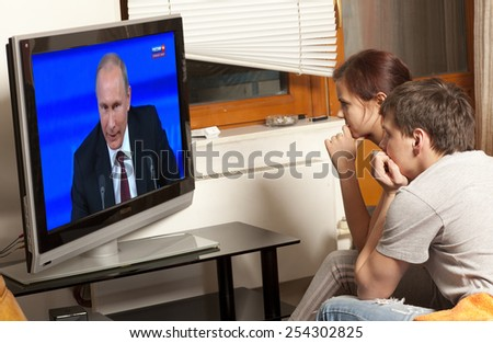 ULAN-UDE, RUSSIA - FEBRUARY 20: Young family watching Russian President Vladimir Putin on TV on February 20, 2015 in Ulan-Ude - stock photo