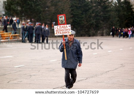 ULAN-UDE, RUSSIA - MAY 9: An unidentified old man carries a Stalins portrait with a slogan below: Glory to great Stalin, after parade on annual Victory Day, May, 9, 2006, Ulan-Ude, Buryatia, Russia. - stock photo