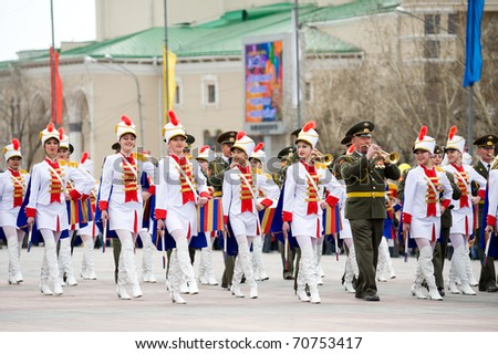 ULAN-UDE, RUSSIA - MAY 9: Young drummer girls march with a military band at the parade on annual Victory Day, May, 9, 2010 in Ulan-Ude, Buryatia, Russia. - stock photo