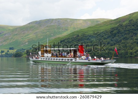 ULLSWATER, LAKE DISTRICT, ENGLAND-JUNE 30 2014: Warm calm summer weather on Monday 30th June 2014 brought visitors to Ullswater Lake District, to take a trip on the steam ferry - stock photo
