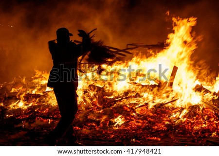 ULSAN, SOUTH KOREA, CIRCA 2015: A fireman adds some stray material into the fading fire at Ulsan's Daeboreum Festival in Korea. The daeboreum festival celebrates the first full moon of the new year