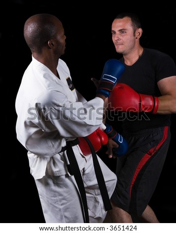 Ultimate fighting, extreme sports, kickboxing versus karate, Caucasian and African American . - stock photo