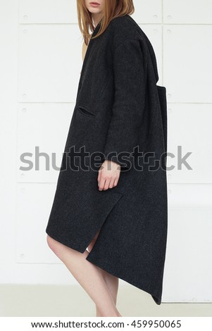 Ultra-fashion concept. Portrait of young fashionable woman with red hair wearing gray coat and posing over white background. Street style. Studio shot