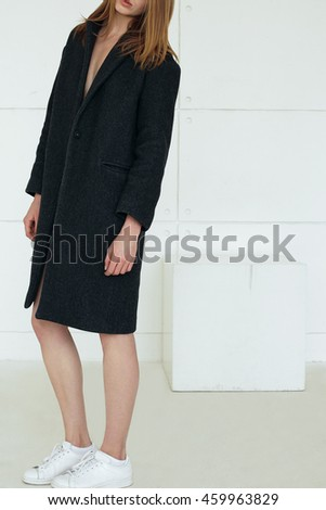 Ultra-fashion concept.  young fashionable woman wearing gray coat and posing over white background. Studio shot - stock photo