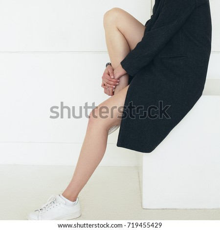 Ultra-fashion concept. Young fashionable woman with long beautiful legs wearing black coat, white sneakers, sitting on cube over white background. Street style. Studio shot