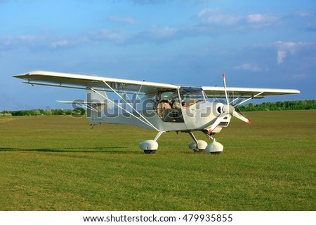 Ultra light aircraft on airport grass in sunset