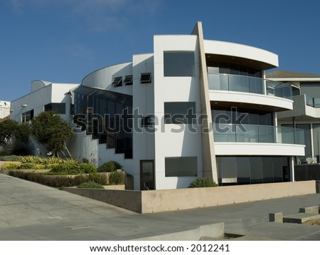 Ultra modern contemporary white house with balconies and landscaping - stock photo