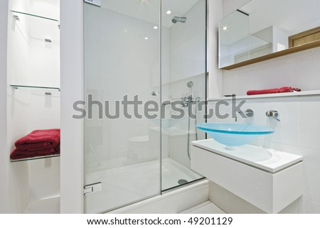 ultra modern luxurious en-suite bathroom with shower cabin and glass hand wash basin - stock photo