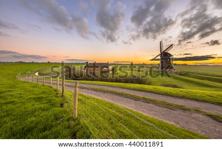 Ultra wide angle scene of Dutch Wooden windmill in flat grassy landscape under beautiful sunset seen from the sea dike at Waddensea, Netherlands - stock photo