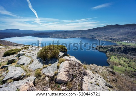 Ultra wide angle view of entire Sanabria lake over rocks in Spain
